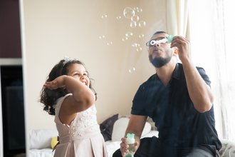 Dad and young girl playing with bubbles at home