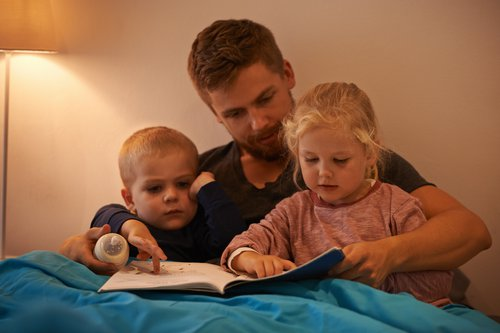 Dad reading with son and daughter
