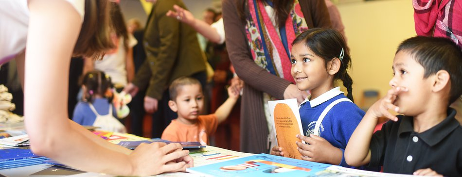 child in school uniform receiving book.jpg